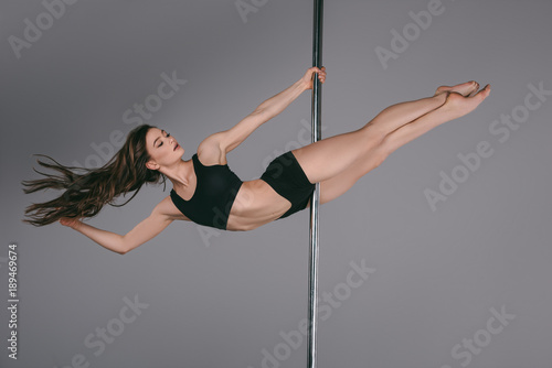 full length view of beautiful sporty girl dancing with pole on grey Fototapeta