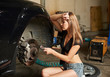 Woman in a frank attire sits on a tire near a black car in a auto repair shop. With one hand she leaned against the auto second holding a socket wrench