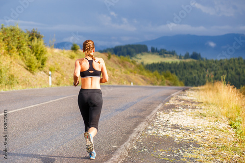 Foto op Canvas Jogging Young sporty woman jogging on mountain road. Running fitness girl in sportswear outdoor image with copy space