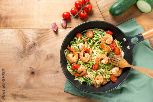 Zucchini noodles with cherry tomato and prawns in a pan