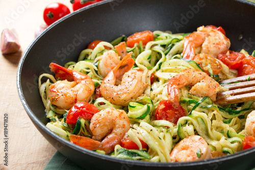 Zucchini noodles sauteed with cherry tomato and prawns in a pan