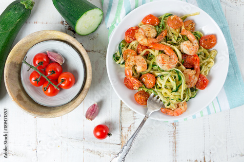 Zucchini spaghetti sauteed with cherry tomato and prawns on white table