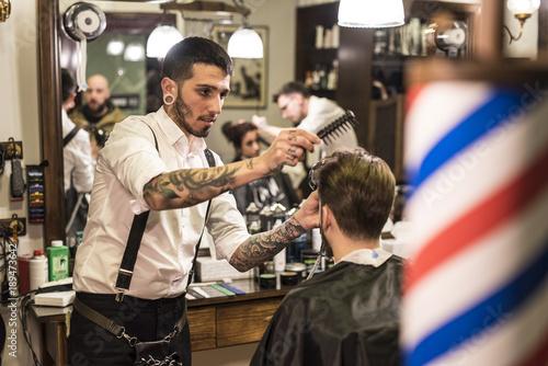 modern hairdressing. Beards, tattoos and hair art. Barber combing and cuting hair. Jaen, Spain.