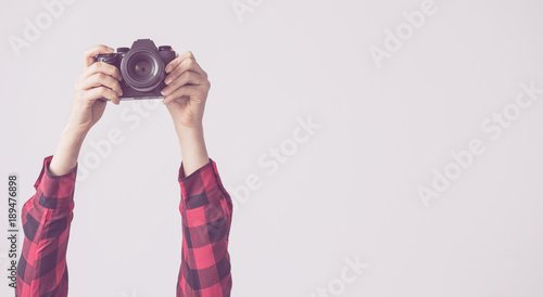 Fototapeta Young female, raised up arms and holding camera isolated background obraz na płótnie