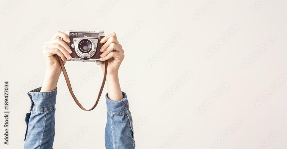 Fototapeta Arms up holding vintage camera isolated background - obraz na płótnie