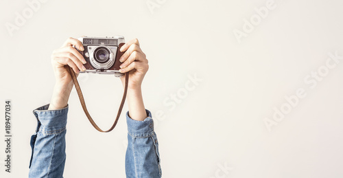 Arms up holding vintage camera isolated background