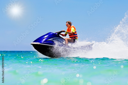 Poster Nautique motorise Teenager on jet ski. Teen age boy water skiing.