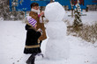 Happy grandmother and granddaughter sculpt a big snowman, Happy family play in a winter park