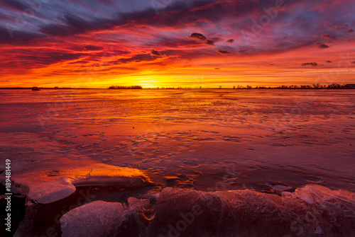 Colorful Sunrise or Sunset on a frozen lake with rocks in the foreground