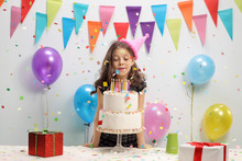 Little Girl Blowing Candles On A Birthday Cake