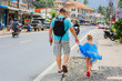 Dad leads her daughter by the hand on the road. Samui Island. Thailand. Traffic.