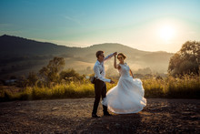 Emotional Wedding Shot Of The Happy Glamour Newlywed Couple Dancing On The Road During The Sunset. Beautiful Nature View.