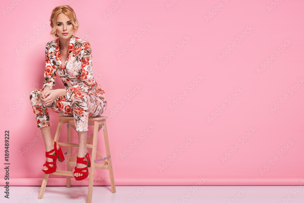 Fototapeta Fashion photo of a beautiful elegant young woman in a pretty suit with flowers holding handbag posing over pink background. Fashion photo