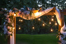 Beautiful Place Made With Wooden Square And Floral Decorations For Outside Wedding Ceremony In Wood. Wedding Settings With Electric Lamp  Bulbs At Scenic Place At Night. Horizontal Color Photography.