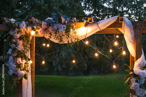 Leinwand Poster Beautiful place made with wooden square and floral decorations for outside wedding ceremony in wood