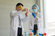 Two scientists are conducting experiments in vitro in the laboratory..