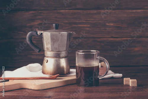 old coffee pot, geyser, glass mug with coffee, wooden background Fototapete