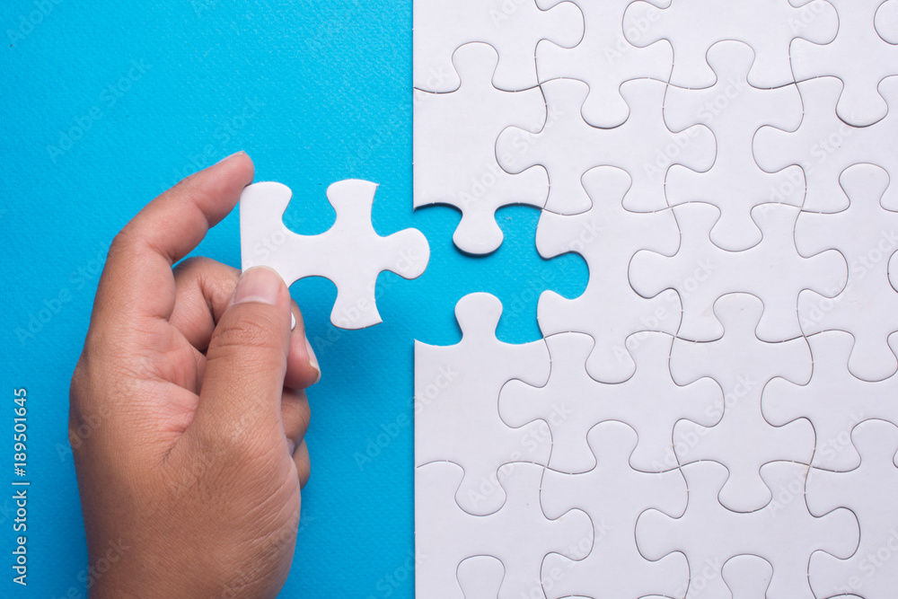 Fototapeta Hand holding piece of white puzzle on blue background. Business and team work concept.