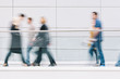 large crowd of people walking in a clean futuristic corridor