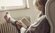 Leinwandbild Motiv Junge Frau schaut aus dem Fenster, trinkt Tee und legt Füße zum Aufwärmen auf die Heizung