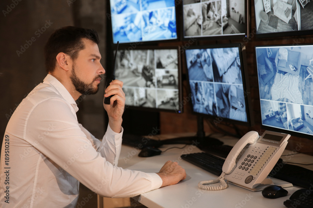 Fototapeta Male security guard using radio transmitter in surveillance room