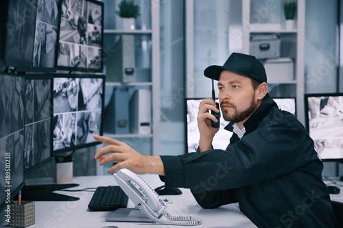 Fotografia Male security guard using radio transmitter in surveillance room