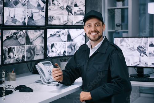 Male security guard working in surveillance room Wallpaper Mural