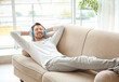 Young man listening to music while relaxing on sofa at home