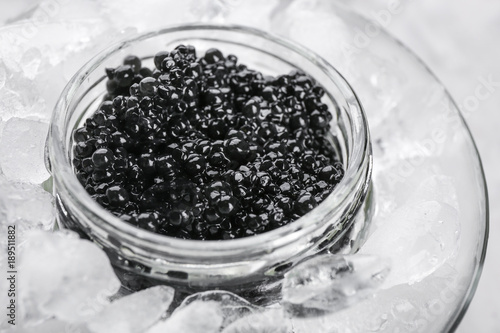 Black caviar served with ice in glass bowl