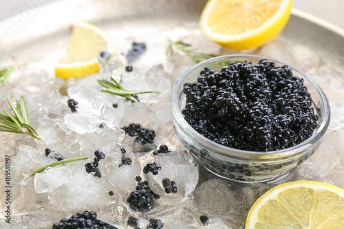 Black caviar served with ice and lemon on metal plate