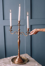 Three Candles In A Candelabra On A Table