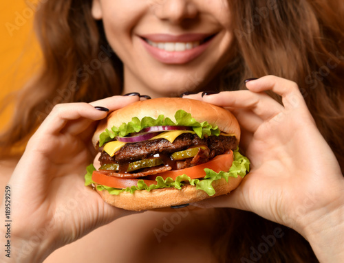 Fototapeta Woman eat burger sandwich with hungry mouth on yellow background obraz