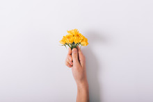 Female Hand Holding A Small Bouquet Of Yellow Roses