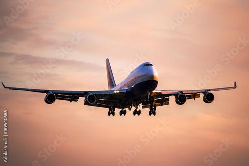 Fotografia  Large passenger airplane landing at international airport at sunset