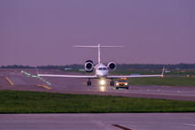 """Business Jet Taxiing On Airport Runway After """"follow Me"""" Car"""