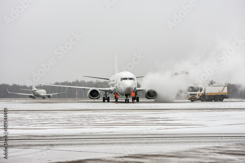 Fotografie, Obraz  De-icing of civil passenger airplane on the apron of international airport durin