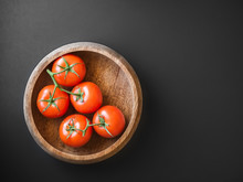 Ripe Tomatoes On Vine In Wood Bowl