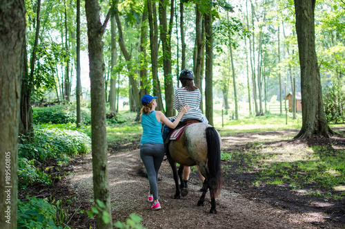 Leinwand Poster child horseback riding with a mentor in a green forest