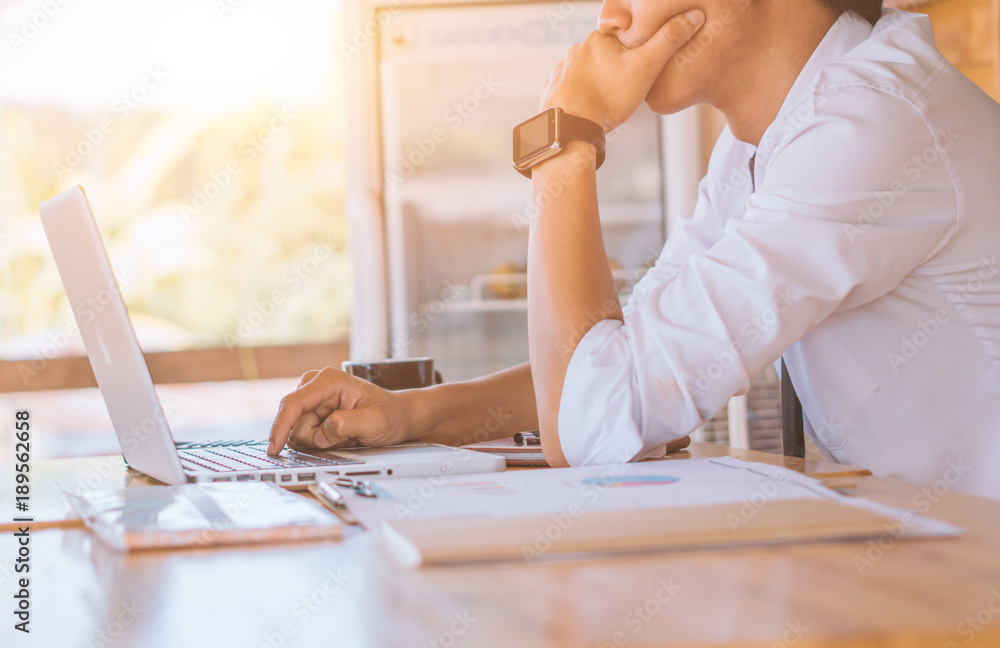 Fototapeta Concentrated at work. Confident mature man in shirt and tie looking at his laptop while sitting at his working place