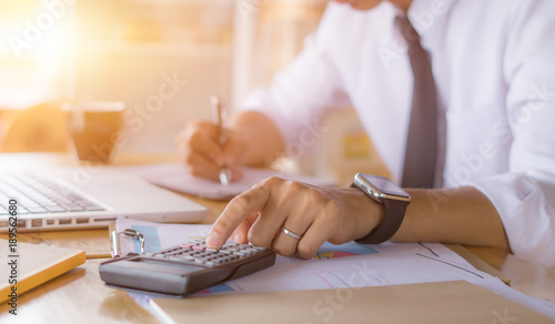 Fototapeta Businessman accountant or banker making calculations. Savings,Business Financing Accounting Banking and economy Concept. ,Image of hands using calculator on desk about cost at office. obraz