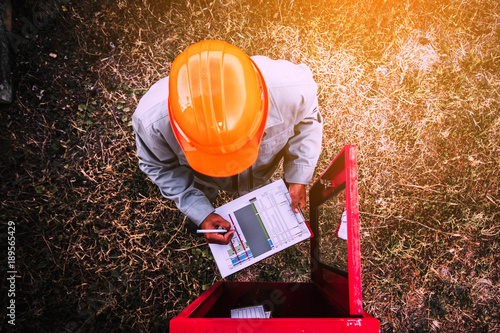 Fotografie, Obraz  safety officer working on checking Fire extinguisher at outdoor plant