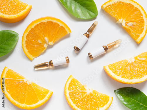 Fototapeta Vitamin C brown ampule for injection with fresh juicy orange fruit slices on white table. High dose vitamin c synthetic for white skin. Beauty product branding mock-up. Healthy lifestyle. Top view. obraz