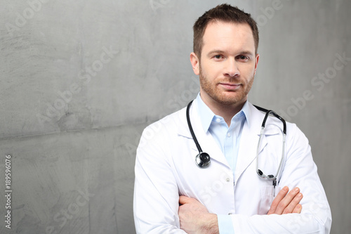 Lekarz. Przystojny lekarz ubrany w biały kitel stoi w klinice