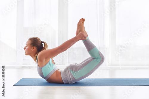 Fotografie, Obraz  Beautiful woman practices yoga asana dhanurasana - bow pose at the yoga studio