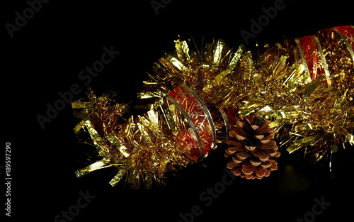 1a84ba7a97cd Golden, yellow tinsel, Christmas ornament, decoration with red ribbon and pine  cone isolated on black background