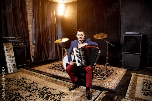 Valokuva  Accordionist in the recording studio. Accordion on the knee