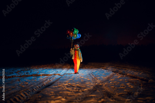 Fotografía Full-length clown photo with colorful balloons at night