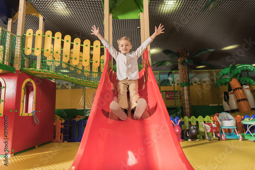aa1d8dd7fb8f2 cute happy little boy with raised hands playing on slide in entertainment  center