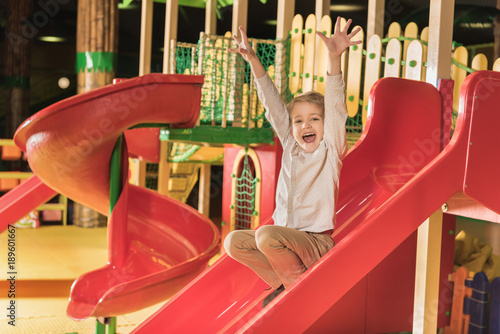 2a4e78e1df7ac adorable happy little boy with raised hands playing on slide in game center