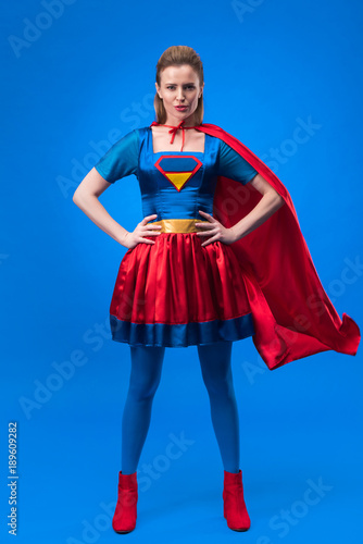 beautiful confident woman in superhero costume standing akimbo isolated on blue Wallpaper Mural